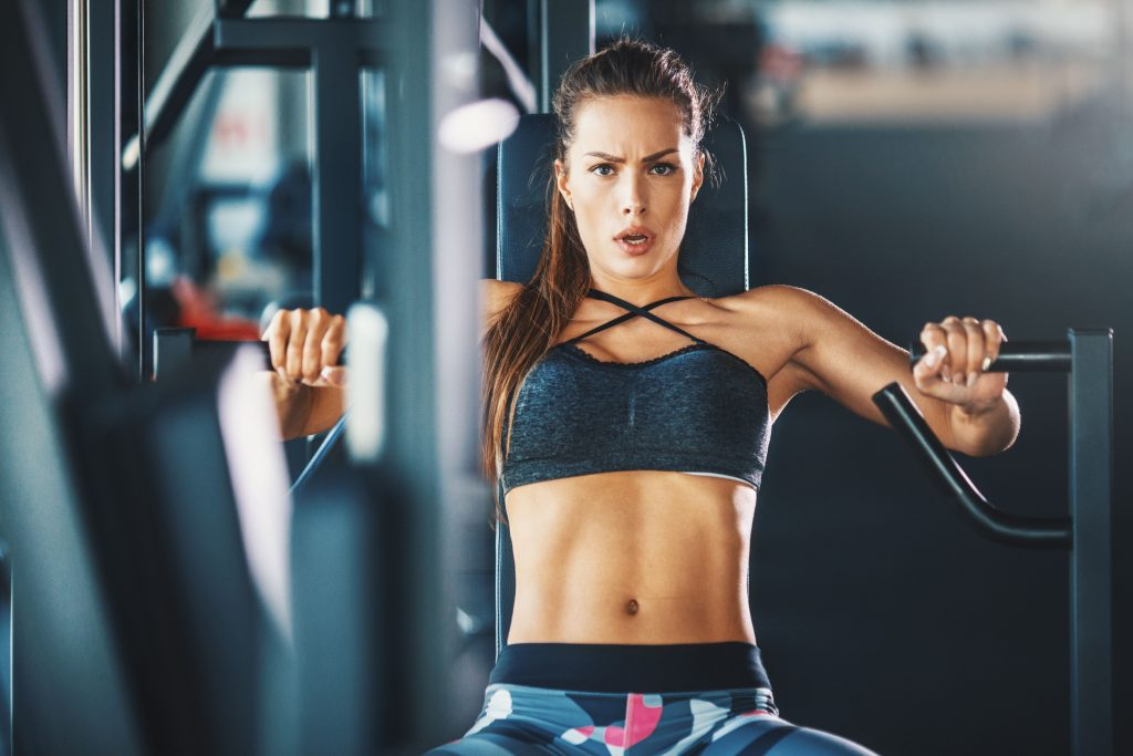 Closeup front view of attractive brunette working out on a chest press at a gym. SHe's looking at camera with hardworking, almost angry, expression. Toned shot.